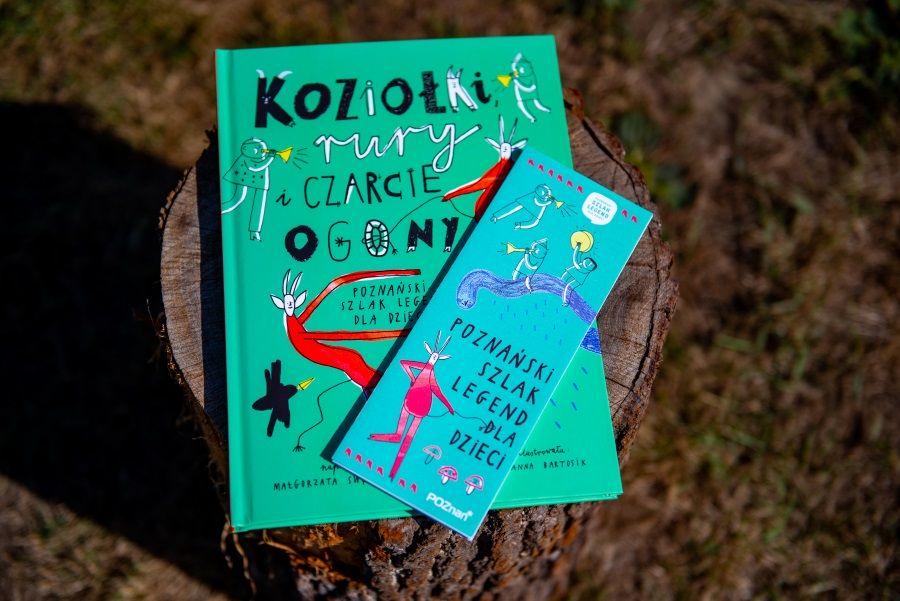 Zdjęcie pokazuję książkę Koziołki rury i czarcie ogony oraz ulotkę Poznańskiego Szlaku Legend dla Dzieci