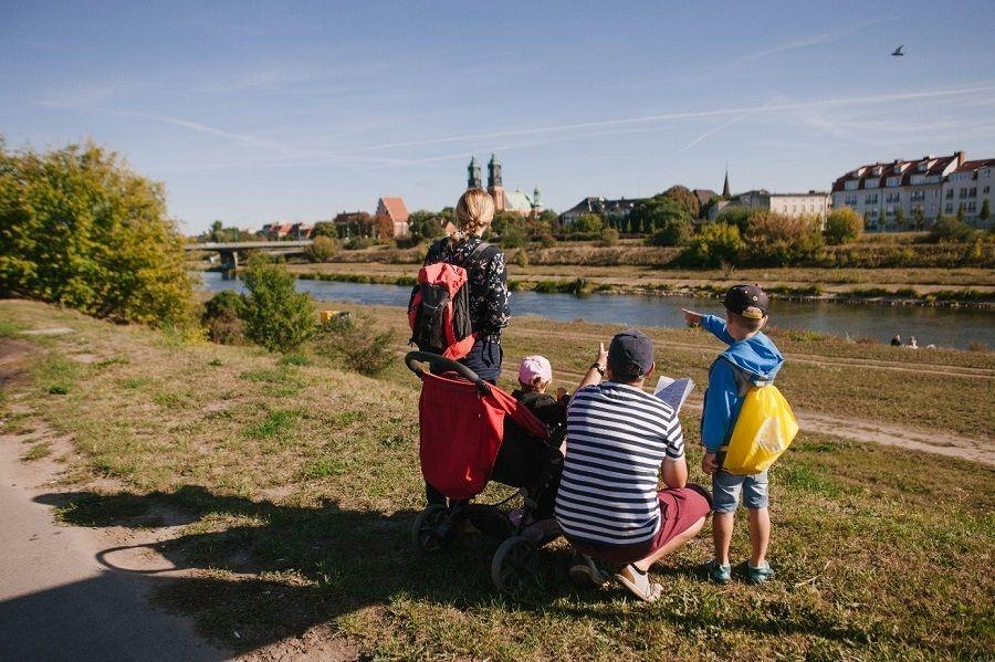 Rodzina biorąca udział w Wakacjach z Poznańskim Szlakiem Legend dla Dzieci mająca w tle rzekę Wartę i Katedrę Poznańską