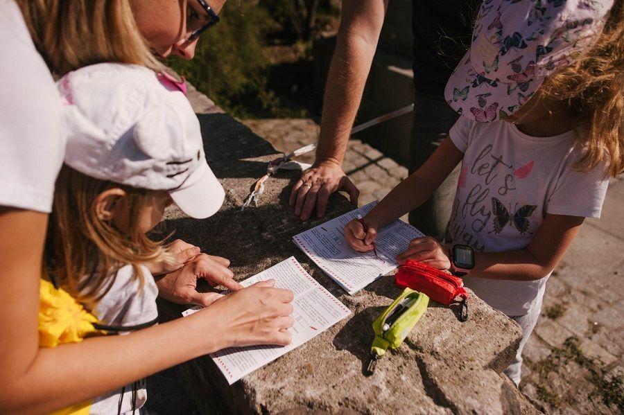 Rodzina biorąca udział w Wakacjach z Poznańskim Szlakiem Legend dla Dzieci w trakcie rozwiązywania zagadki
