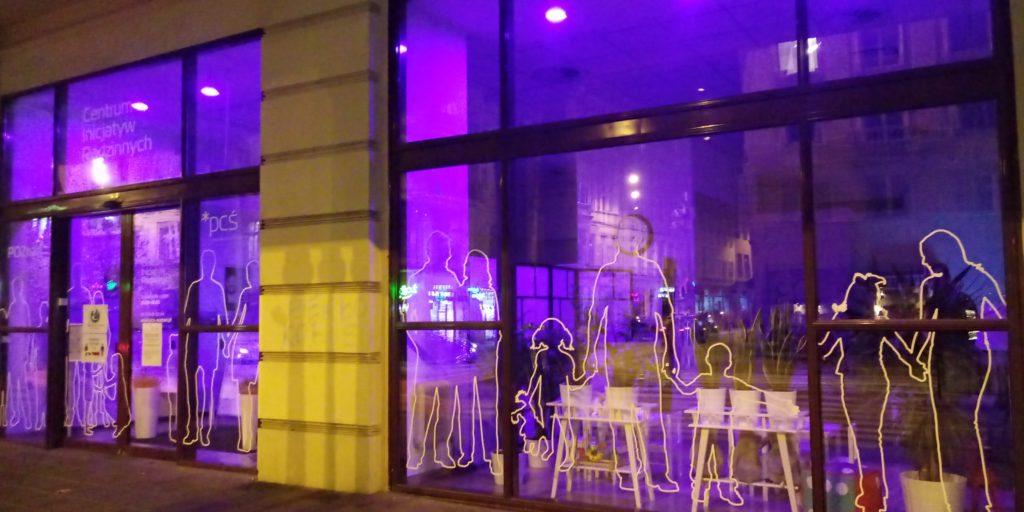 Fotografia pokazuje podświetlone na fioletowo okna Centrum Inicjatyw Rodzinnych.