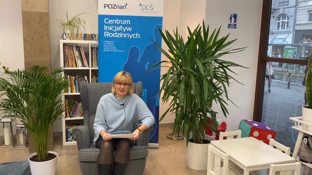 Na zdjęciu jest się Pani Anna Gruszecka - Dyrektor Biblioteki Raczyńskich w Poznaniu. Anna Gruszecka siedzi na fotelu, czyta bajkę. W tle regału z książkami i roll-upu CIR. Po swojej lewej i prawej stronie ma duże zielone rośliny.