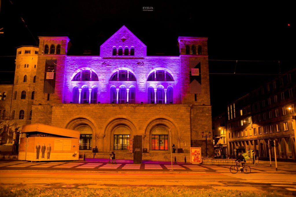 Na zdjęciu znajduje się budynek CK Zamek podświetlony na fioletowo