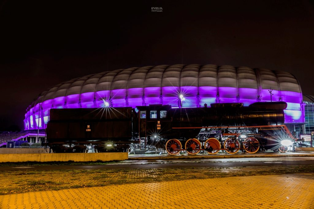 Zdjęcie pokazuje Stadion Miejski w Poznaniu podświetlony na fioletowo. Przed Stadionem stoi lokomotywa Kolejorza