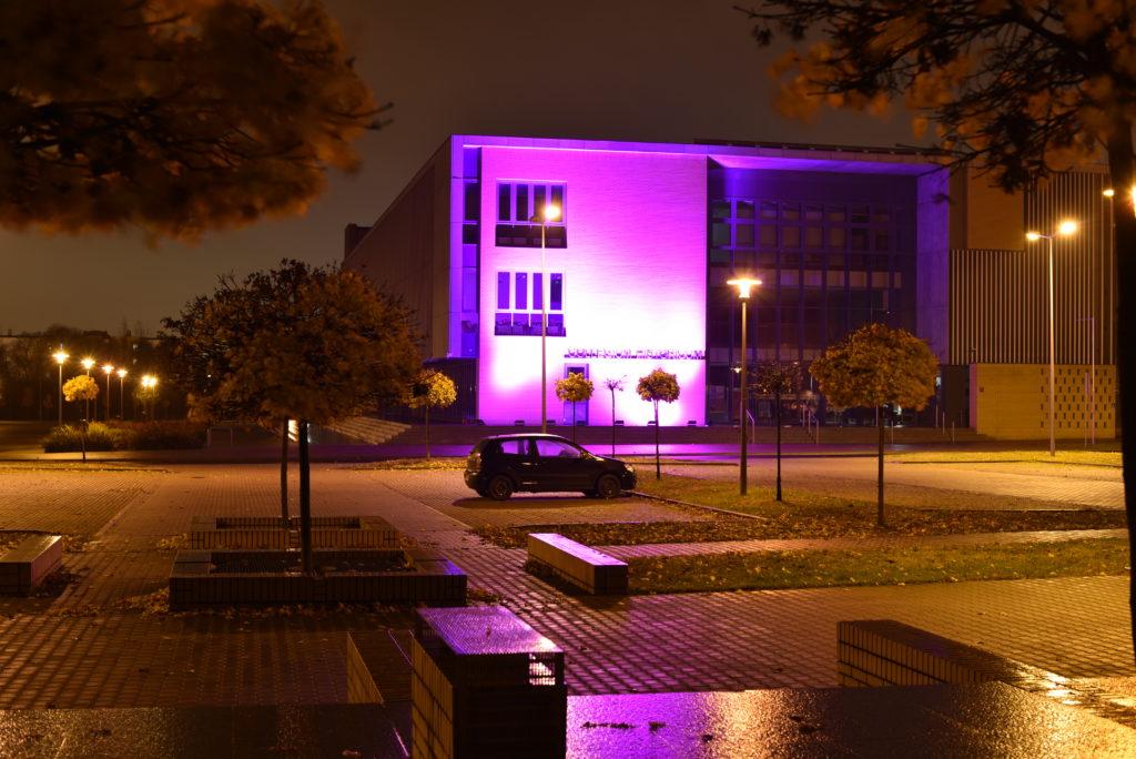 Zdjęcie pokazuje nowy budynek Biblioteki Collegium Historicum UAM podświetlony na fioletowo