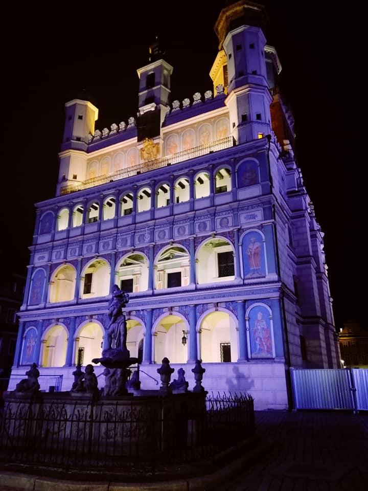 Zdjęcie ukazuje budynek poznańskiego ratusza podświetlony na fioletowo