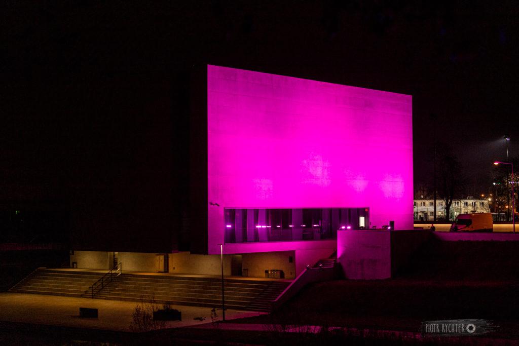 Zdjęcie przedstawia budynek Bramy Poznania podświetlony na fioletowo