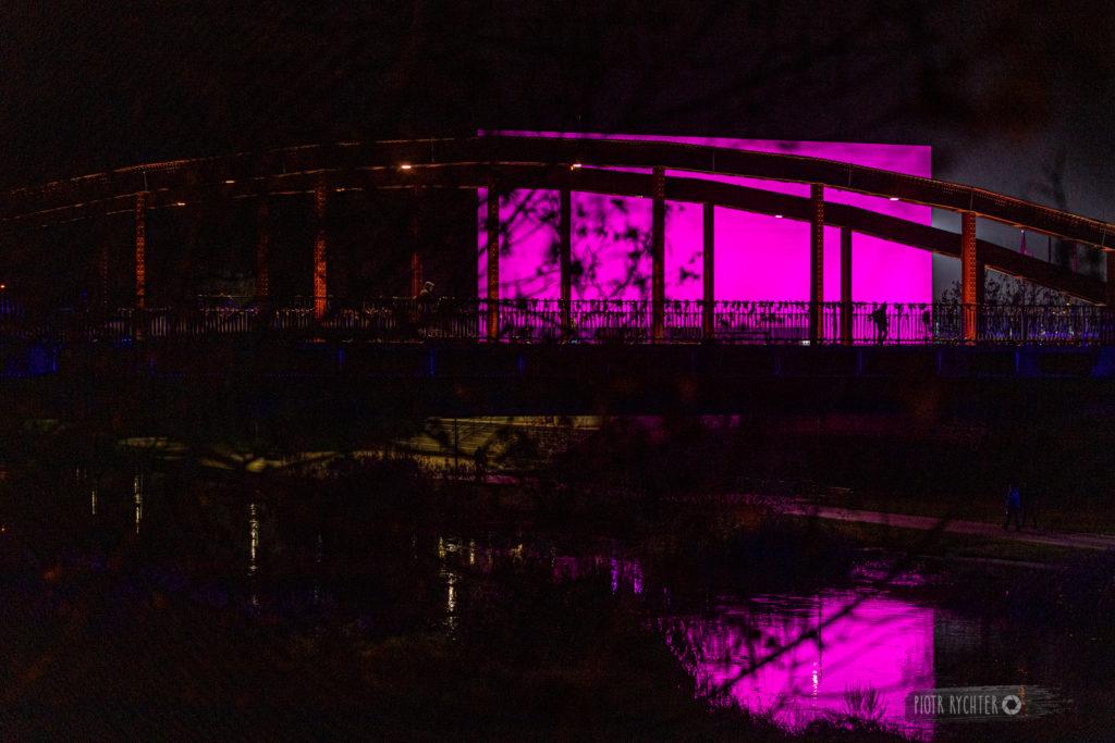 Zdjęcie pokazuje budynek Bramy Poznania podświetlony na fioletowo