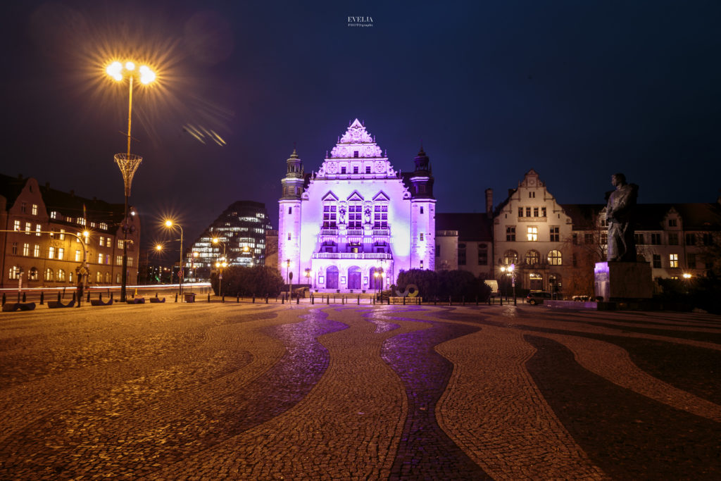 Zdjęcie pokazuje budynek Auli Uniwersytetu Adama Mickiewicza przy ul. Wieniawskiego, podświetlonej na fioletowo