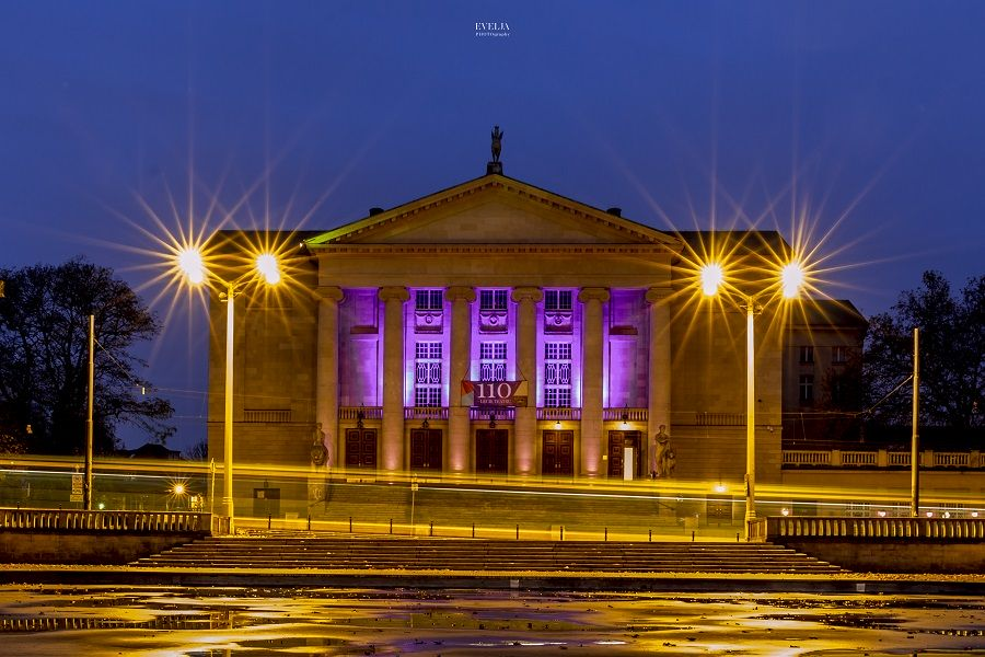 Zdjęcie przedstawia budynek Teatru Wielkiego w Poznaniu podświetlonego na fioletowo