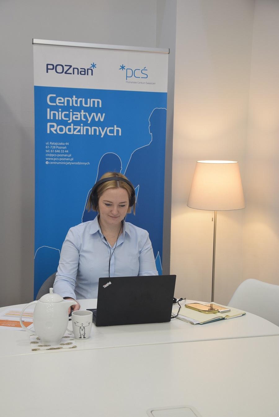 Na zdjęciu znajduje się Pani Urszula Mańkowska - Zastępca Dyrektora PCŚ ds. Zarządzania Centrum Inicjatyw Rodzinnych, która siedzi przy stole, pracuje na laptopie. W tle widać roll-up CIR i świecącą lampę