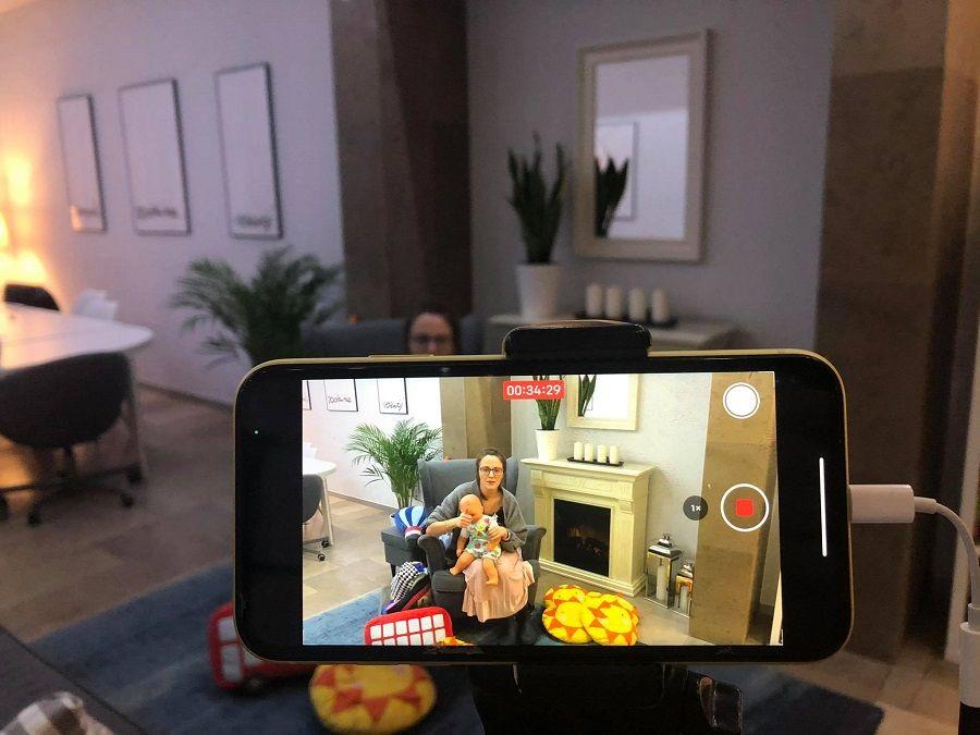 Zdjęcie przedstawia telefon komórkowy, na ekranie którego widać prowadzącą spotkania - Panią Agatę Kalinę siedzącą na fotelu przy kominku. Na kolanach trzyma lalkę