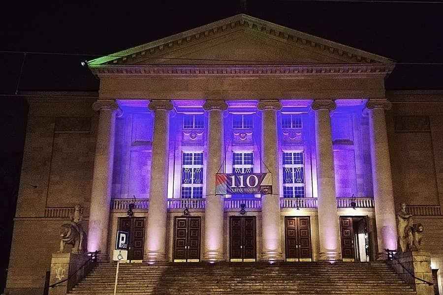 Zdjęcie pokazuje budynek Teatru Wielkiego w Poznaniu podświetlonego na fioletowo