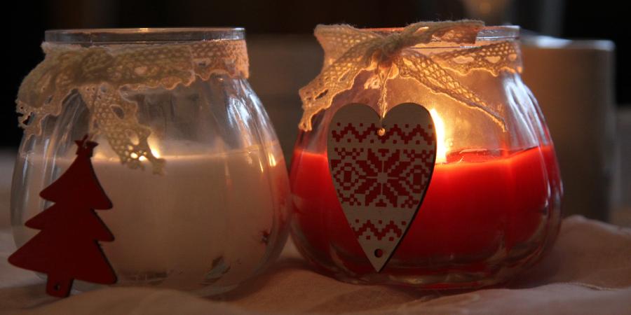 Na ilustracji przedstawione są dwie zapalone świeczki w słoiczkach niewielkich rozmiarów. Fotografia to zbliżenie na nie oraz ozdoby, drewnianą choinkę oraz bombkę, przyczepione do koronkowej wstążeczki, którą są owinięte. Fotografia jest wyciszająca i przyciszona, ma świąteczną atmosferę, co również podkreśla płomyk ognia, który tli się w szkle.