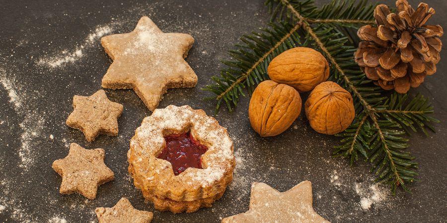 Ilustracja przedstawia szary blat na którym ułożono pięć ciastek w kształcie gwiazdek posypanych mąką, co świadczy o tym, że za chwilę zostaną upieczone. Jedno ze słodkości się wyróżnia, ponieważ jest okrągłe, dwuwarstwowe a w środku wycięta jest gwiazdka, przez która widać czerwone nadzienie, zapewne malinowe. Dodatkowo na ilustracji znajduje się świąteczna dekoracja w postaci gałązki świerkowej na której ułożone są trzy orzechy włoskie oraz szyszka. Dekoracja jest naturalna.
