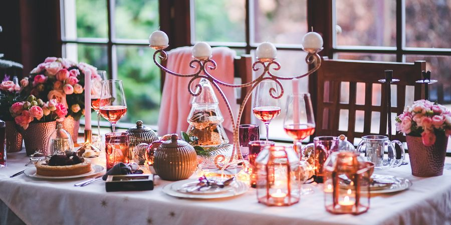 Ilustracja przedstawia bogato zastawiony stół. Na białym obrusie znajdują się małe i subtelne gwiazdki. Na środku ustawiono metalowy świecznik, który swoim kształtem przypomina poroże. Na stole znajdują się również doniczki ze świeżymi kwiatami o delikatnych płatkach przypominających piwonie. Prócz tego jest wiele niższych świeczników szklanych oraz naczynia stołowe. Na jednym z talerzyków widzimy ciasto przypominające sernik z polewą czekoladową. Na drugim planie w głębi widzimy dosunięte krzesła a na jednym z nich na oparciu wisi miękki koc w kolorze różowym. Fotografia ilustruje ciepłą domową atmosferę i utrzymana jest w kolorystyce pastelowej.