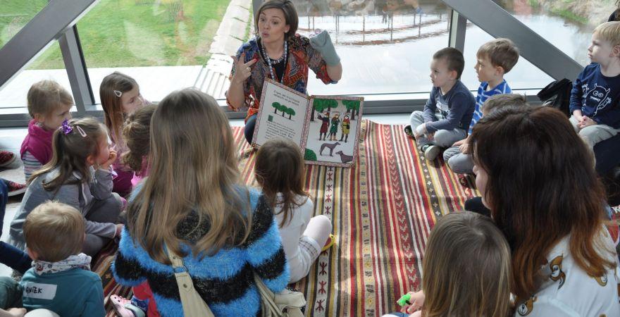 Zdjęcie przedstawia grupę dzieci słuchającą kobietę przedstawiającą za pomocą pacynki  im bajkę