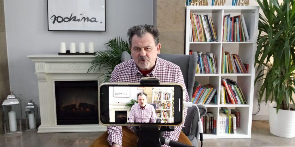 Zdjęcie przedstawia mężczyznę siedzącego na fotelu, na tle płonącego kominka i regału z książkami. Na pierwszym planie widać ekran telefonu, który nagrywa siedzącego mężczyznę.