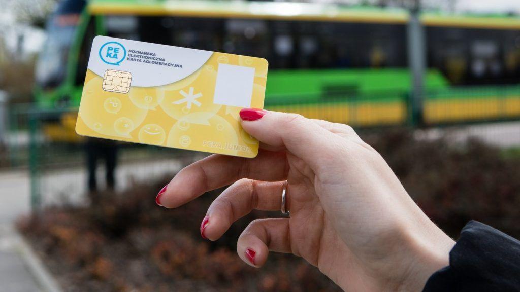Grafika przedstawia trzymaną w dłoni kartę PEKA, którą widać na tle tramwaju.