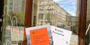 """Na tle przeszklonego wejścia do Centrum Inicjatyw widzoczne są dwie broszury. Jedna jest pomarańczowa z napisem """"Poznańskie Centrum Dziedzictwa"""", a druga biała z napisem """"Brama Poznania""""."""