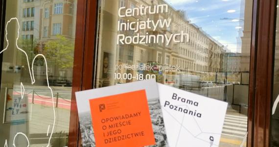 """Na tle przeszklonego wejścia do Centrum Inicjatyw widoczne są dwie broszury. Jedna jest pomarańczowa z napisem """"Opowiadamy o mieście i jego dziedzictwie"""", a druga biała z napisem """"Brama Poznania""""."""