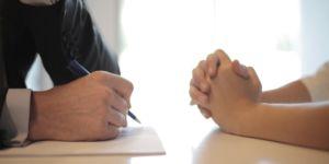 Przy stole siedzą dwie osoby., lecz zdjęcie wykadrowane jest wyłącznie na dłonie. Po prawej siedzi kobieta. Po lewej mężczyzna w garniturze. W dłoni trzyma długopis oraz robi notatki w trakcie rozmowy o pracę.