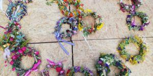 Na podłodze leżą roznokolorowe wianki z kwiatów oraz traw