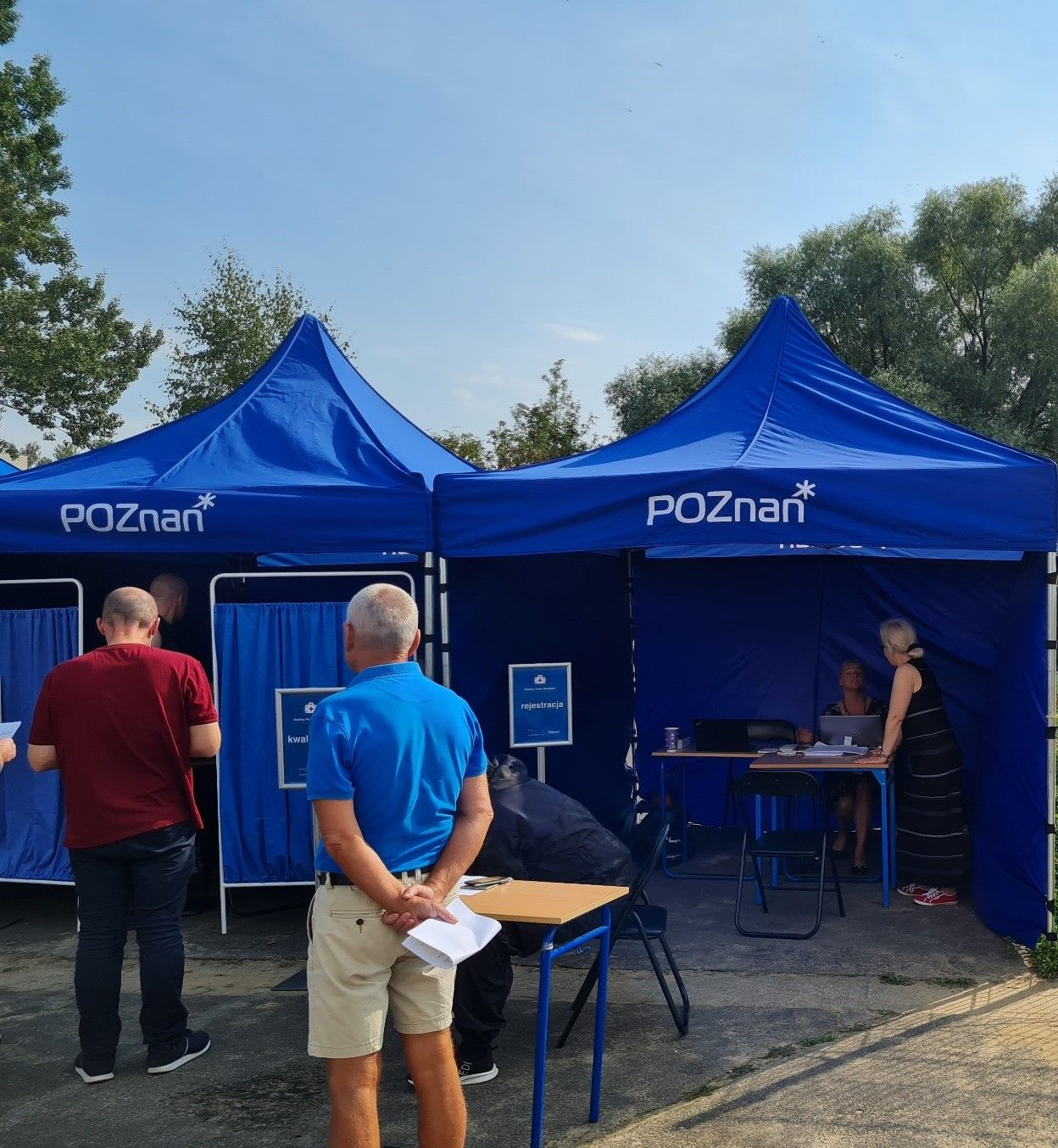 Zdjęcie przedstawia mobilny punkt szczepień: dwa niebieskie namioty z logo Poznań, na pierwszym planie osoby oczekujące na szczepienie
